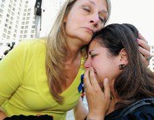 Cheryl Blades, izquierda, abraza a una señora que acudió al juicio y que llora tras la sentencia. La señora, de negro, no identificada afirmó que mientras estuvo embarazada recibió tratamientos contra el cáncer que no necesitaba. (Foto Prensa Libre: AP).