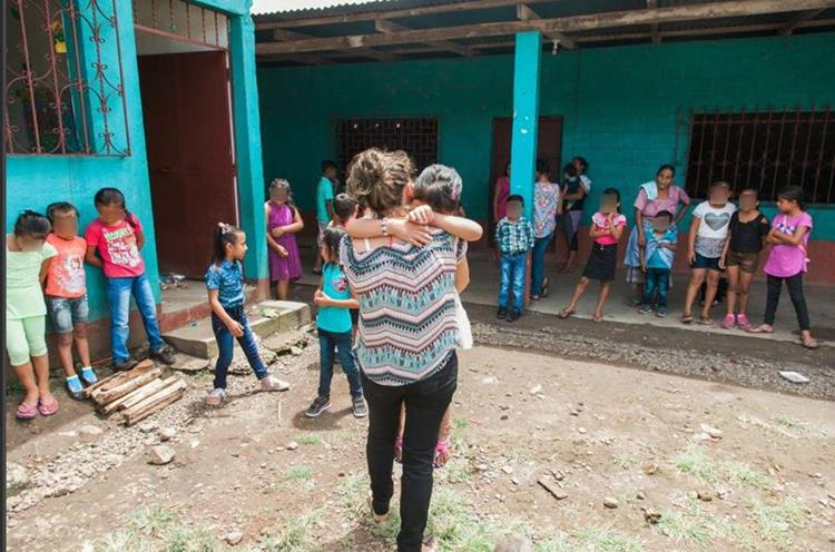 Una maestra abraza a Dayananci en el primer día de clases de la pequeña. La menor originaria de San Marcos estuvo separada de sus padres por varios meses y sufrió para adaptarse de nuevo. (Foto Prensa Libre: Hemeroteca PL)