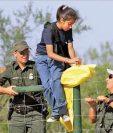 Agentes de la Patrulla Fronteriza ayudan a una niña a cruzar la malla que divide México y EE. UU. (Foto:diaadianews.com).