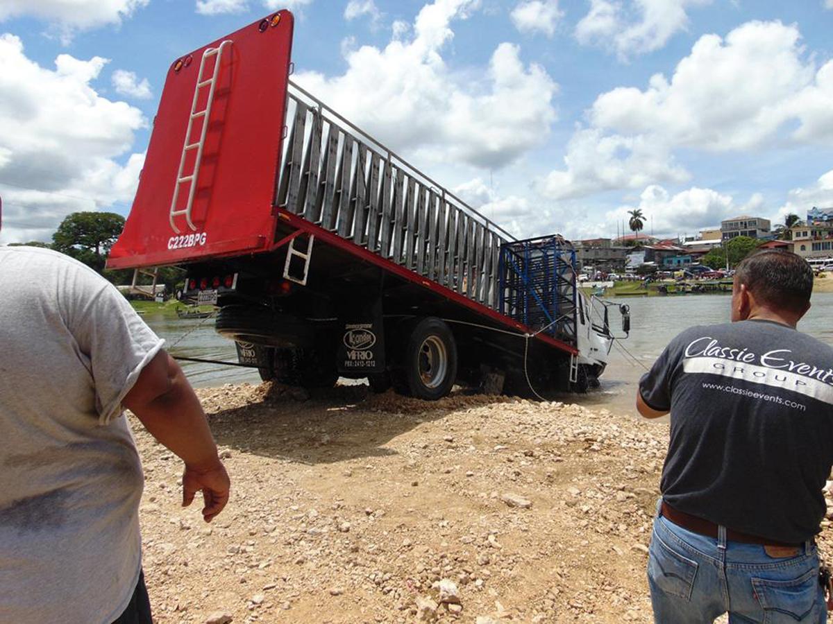Vecinos ayudan a sacar el camión que cayó en el río La Pasión. (Foto Prensa Libre: Dony Stewart).