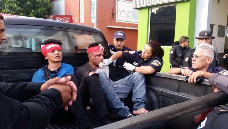Los atacantes, bajo custodia policial, reciben atención de bomberos después de haber sido golpeados. (Foto Prensa Libre: Érick Ávila)