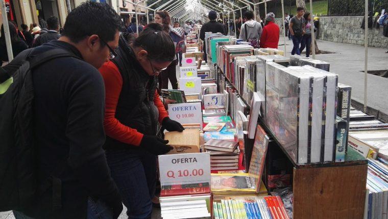 Dos personas observan los libros que se exhiben en el Paseo de la Sexta, zona 1. (Foto Prensa Libre: Edwin Pitán)