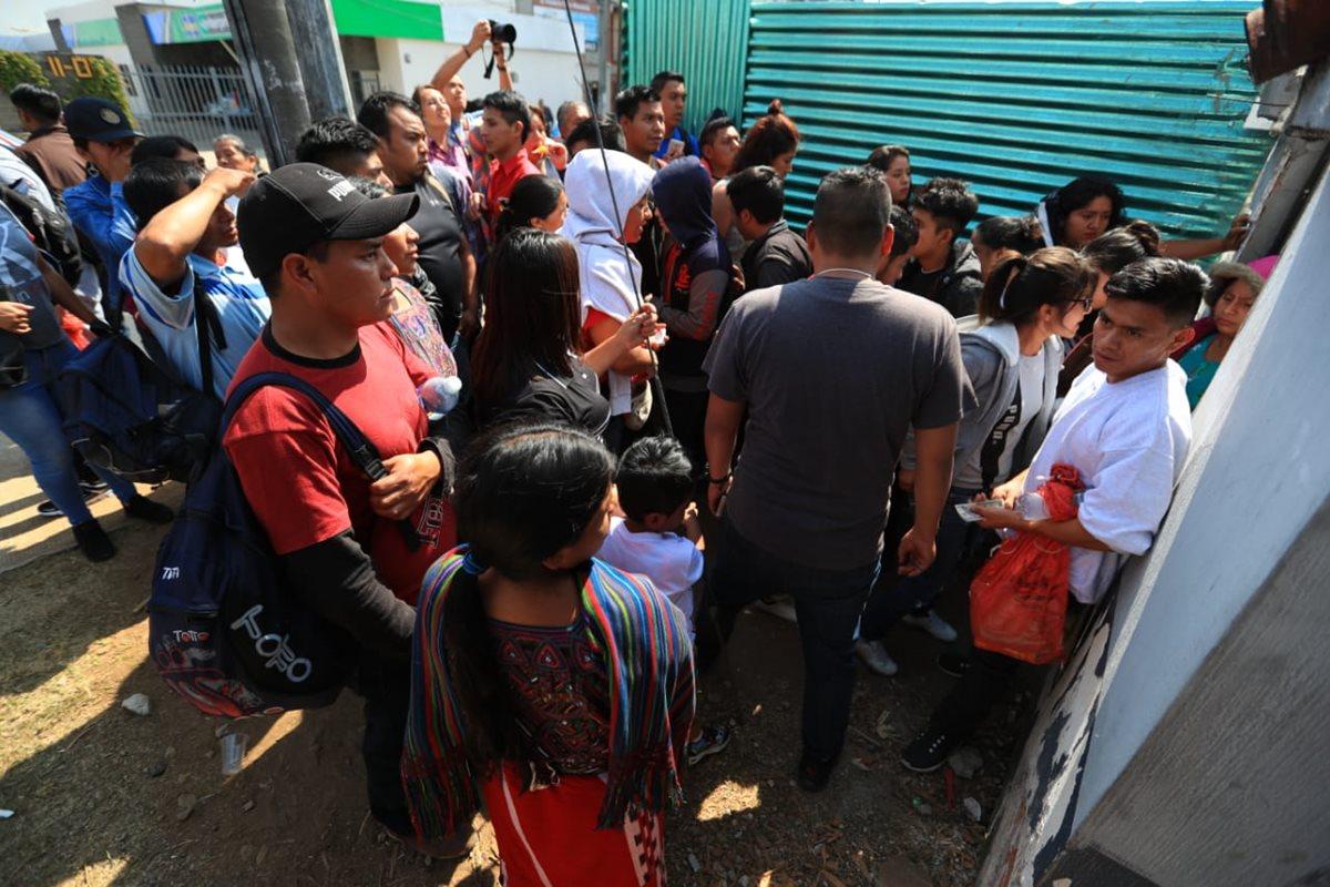 Los guatemaltecos deportados salen por el espacio de una obra en construcción. (Foto Prensa Libre: Carlos Hernández)