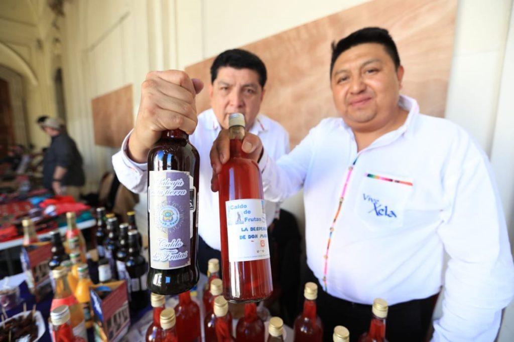 Colaboradores de Despensa Mario, muestran botellas del tradicional caldo de frutas de Salcajá, Quetzaltenango.