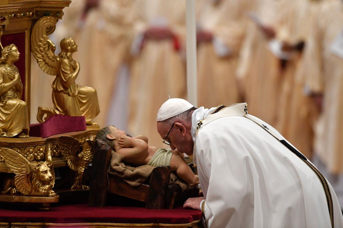 El papa Francisco besa una imagen de bebé Jesús durante una misa en Nochebuena en el Vaticano. (Foto Prensa Libre:AFP).