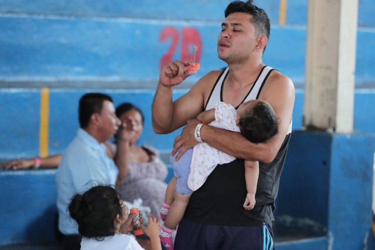 Un padre distrae a su bebé con burbujas mientras hace fila para recibir medicinas.