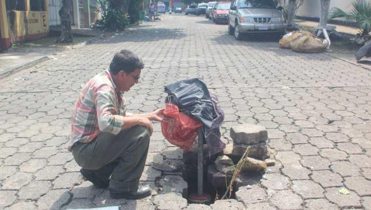 Vecino coloca una señal en el área del hundimiento, en la zona 4 de la ciudad de Escuintla. (Foto Prensa Libre: Melvin Sandoval)