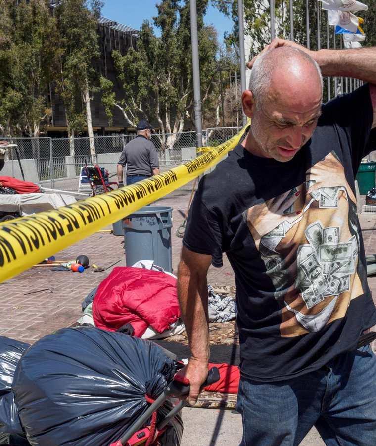 Mark West sale con un carrito con sus pertenencias de un campamento de personas sin hogar en Santa Ana, California, EE.UU.(EFE).