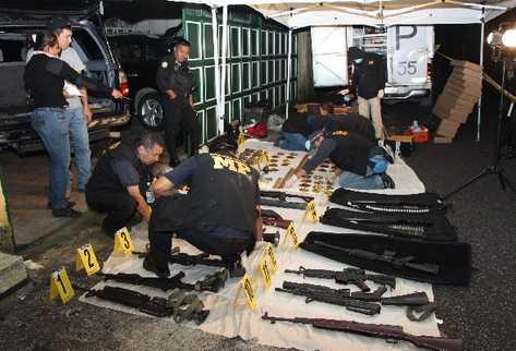 Fiscales revisan el arsenal incautado en la casa 87 B de residenciales Arrazola 1, Fraijanes, la noche del viernes último.