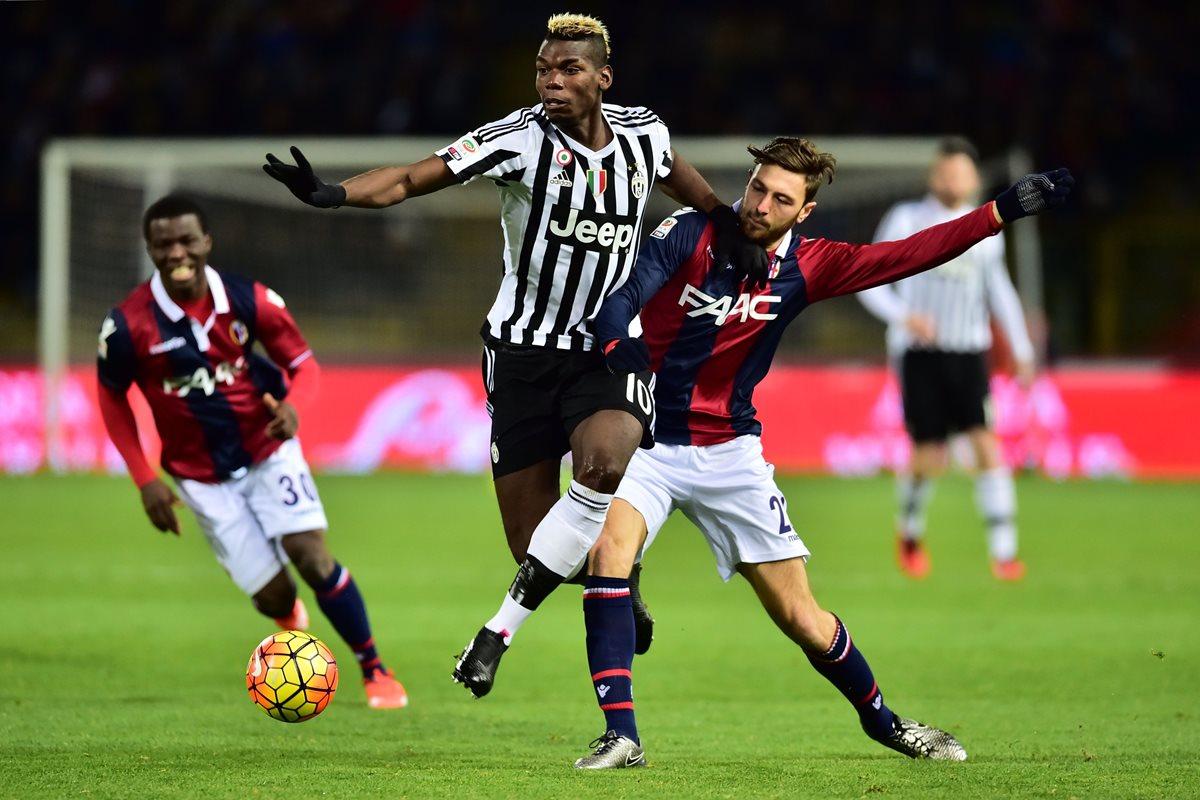 El fránces Paul Pogba, al centro, intenta dominar el balón ante jugadores de la Bologna. (Foto Prensa Libre: AFP)
