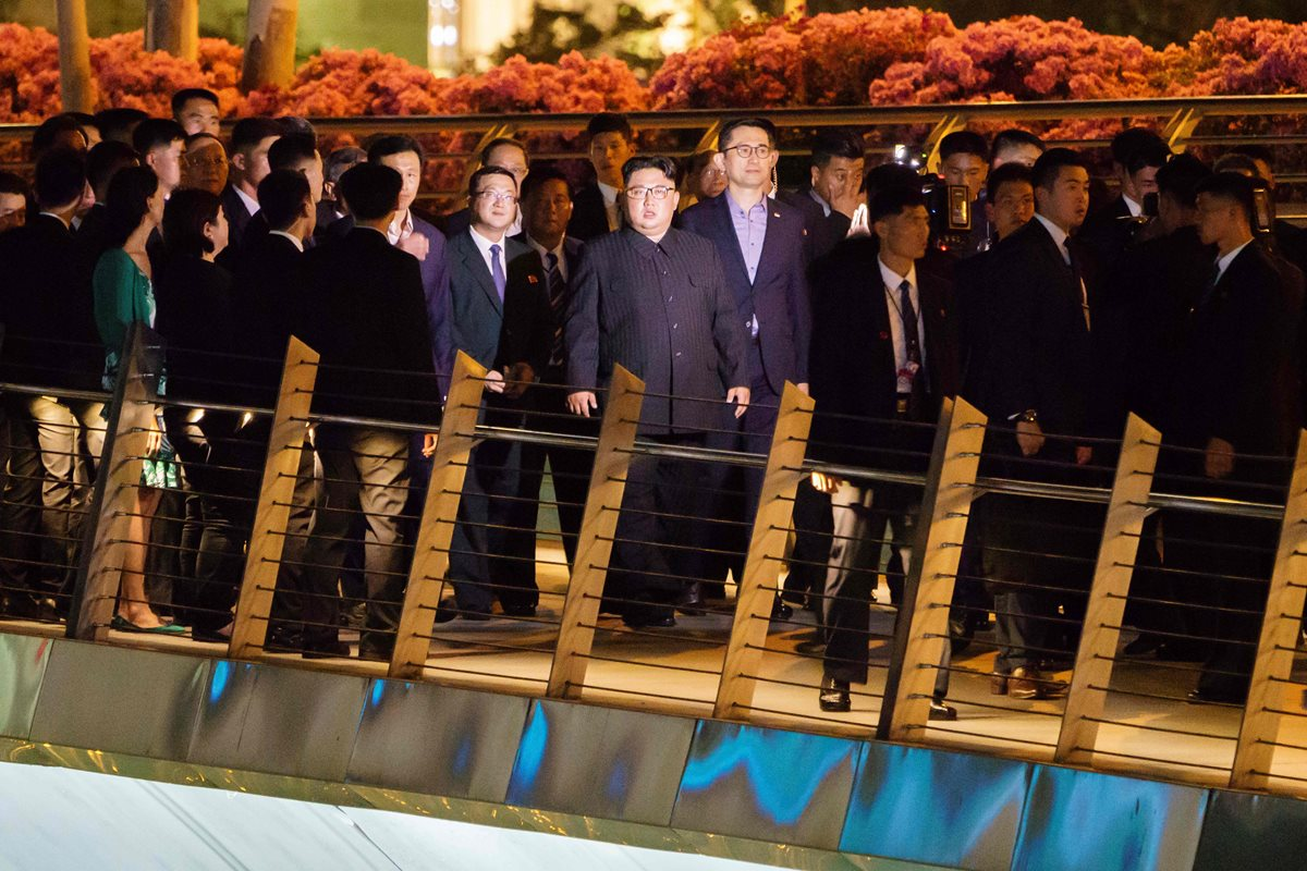 North Korean leader Kim Jong-Un (C) walks on the Jubilee bridge during a tour in Singapore on June 11, 2018.North Korean leader Kim Jong Un took a night-time stroll around some of Singapore's sights late June 11, 2018 ahead of his summit with US President Donald Trump. / AFP PHOTO / Nicholas YEO