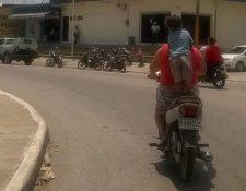 Niño fotografiado en San Benito, Petén, es trasladado de pie y sin casco en motocicleta. (Foto Prensa Libre: Rigoberto Escobar)