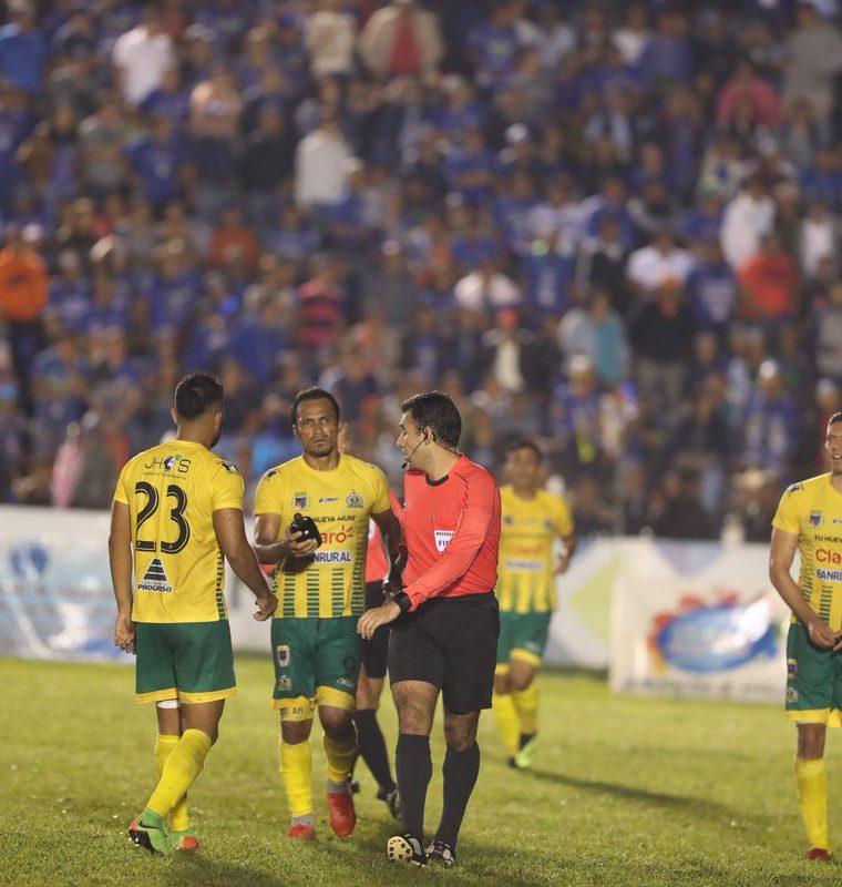 Ángel Rodríguez le entrega a Mario Escobar la botella con la que golpearon al árbitro durante el juego Cobán Imperial vs Xelajú MC. (Foto Prensa Libre: Edwin Fajardo)