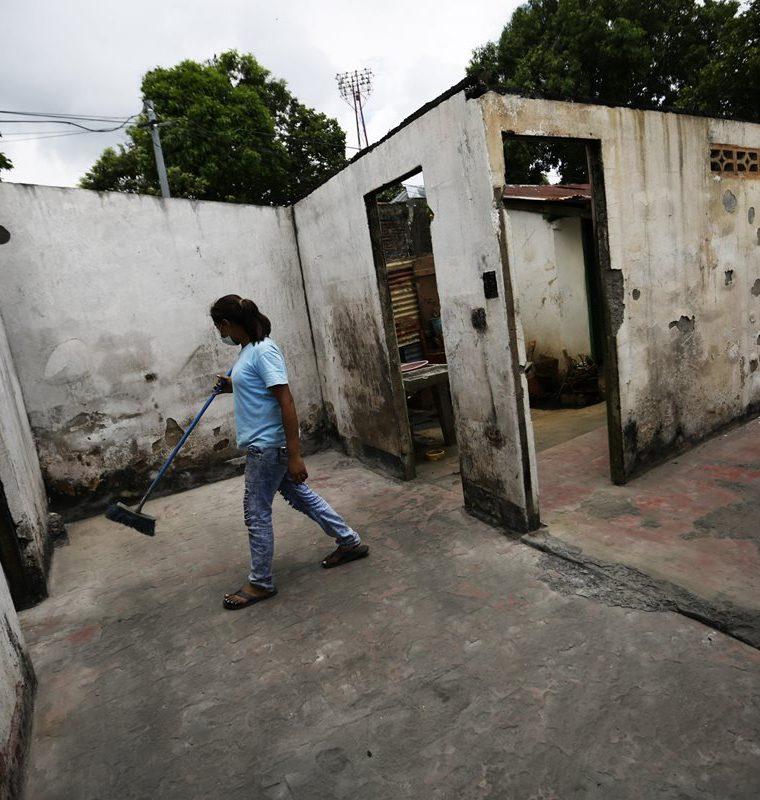 Familiares del artesano Wilfredo Suazo Hernández limpian en su casa la cual fue incendiada por paramiliatres en Masaya, Nicaragua. (EFE)