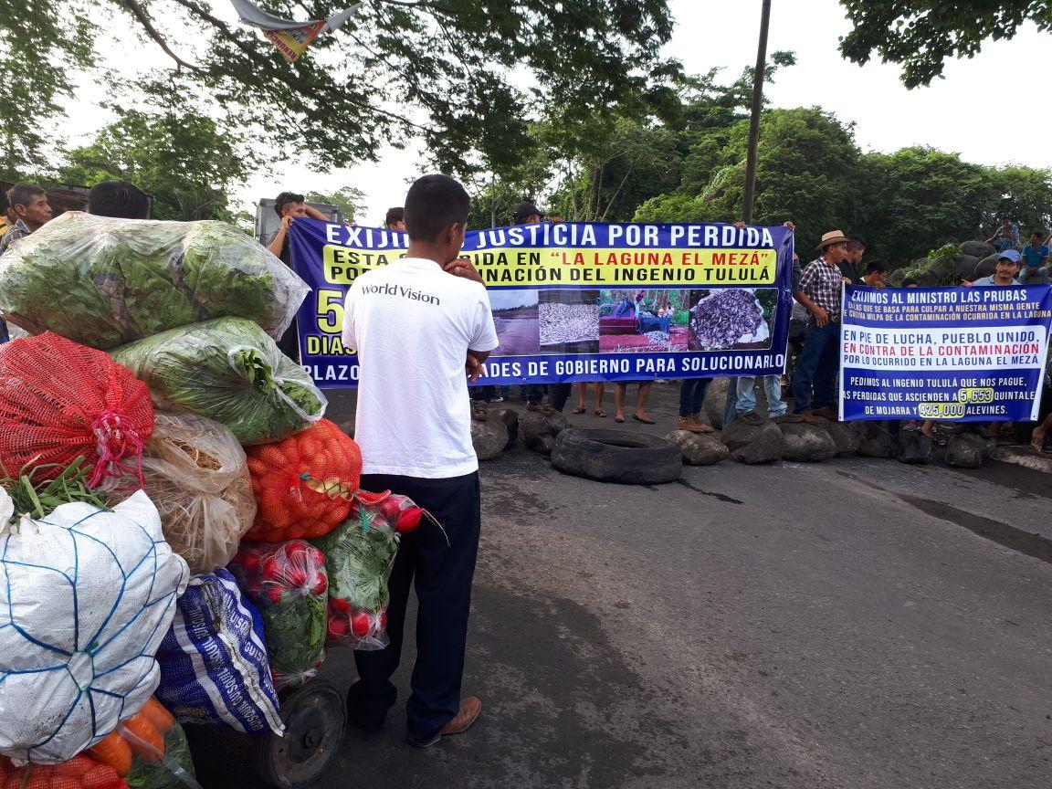 Con palos, llantas y piedras los criadores de tilapia de San José Mangales, Santa Cruz Muluá, bloquearon el paso desde las 6 horas. (Foto Prensa Libre: Rolando Miranda)