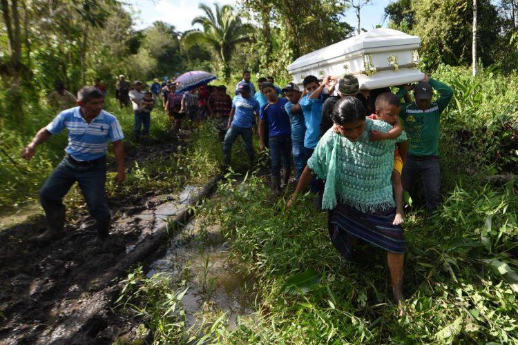 Las personas que acompañan el cuerpo de Jakelin Caal se desplazan por un camino rural en Raxruhá, Alta Verapaz, rumbo al cementerio.