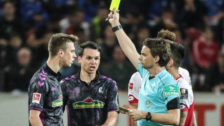 El árbitro Guido Winkmann (d) muestra la tarjeta amarilla a Janik Haberer (i) de Friburgo. (Foto Prensa Libre: AFP)