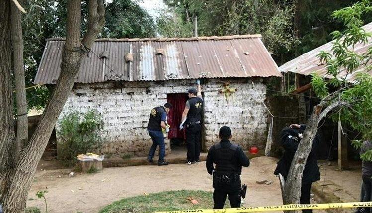 Fiscales del Ministerio Público revisan la vivienda en que fue encontrada Hetnéa y sus dos hijos muertos en el caserío Los Cerritos. (Foto Prensa Libre: Cortesía)
