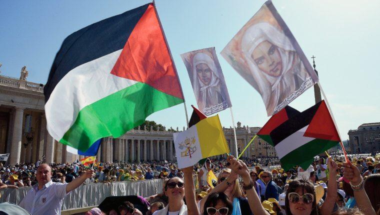 Peregrinos ondean  banderas palestinas antes de una misa en la plaza de San Pedro para la canonización de cuatro monjas. (Foto Prensa Libre:AFP).