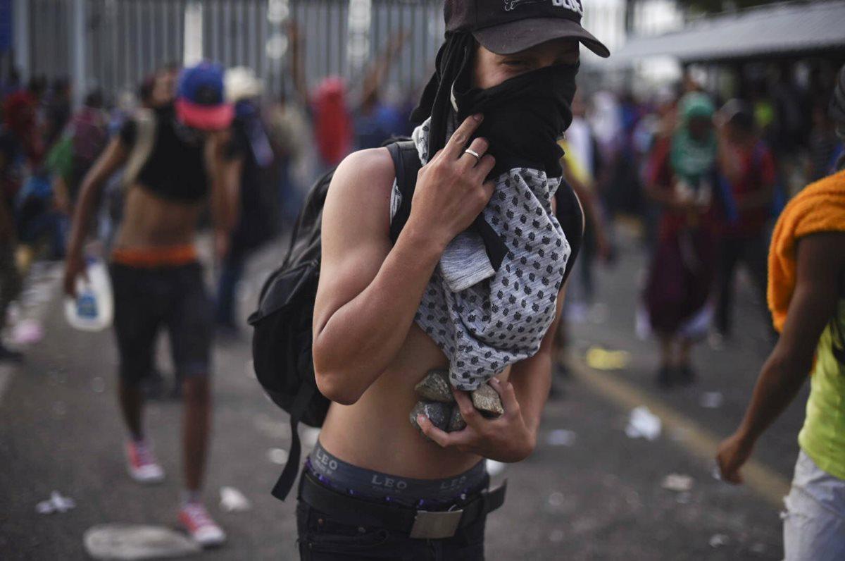 Un migrante hondureño con piedras, durante los disturbios el domingo último en la frontera de Guatemala con México. (Foto Prensa Libre: AFP)