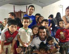 El futbolista Cristian Noriega sonríe junto a un grupo de niños en el albergue de Escuintla, donde entregaron víveres y compartieron varias dinámicas con los pequeños. (Foto Prensa Libre: Cortesía Cristian Noriega)