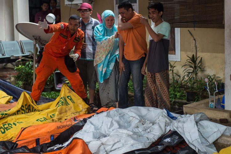 Personas reaccionan tras encontrar a familiares en bolsas para cadáveres de víctimas del tsunami que alcanzó el Estrecho de la Sonda, en Pandeglang, provincia de Bantén, Indonesia.