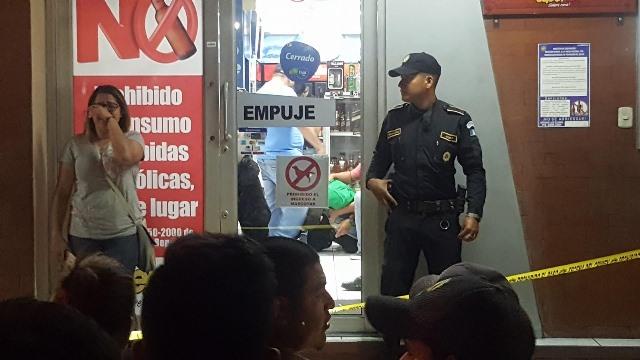 Un agente policial vigila la escena del crimen, mientras que otras personas se muestran muy afectadas por lo ocurrido en el interior del negocio. (Foto Prensa Libre: Mario Morales)