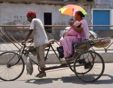 Una mujer protege a su bebé del intenso calor registrado en los últimos días en la India. (Foto Prensa Libre: AFP).