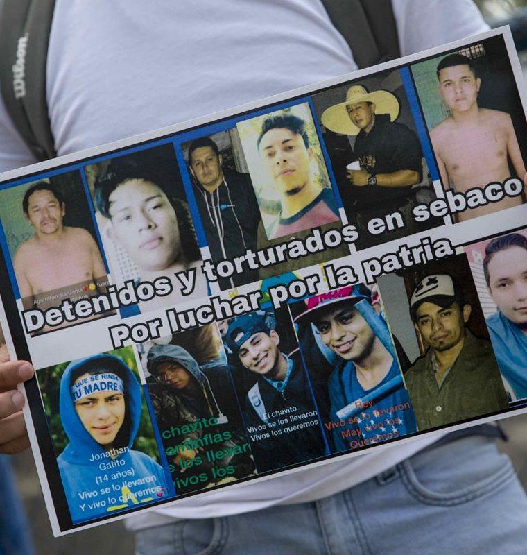 Un nicaragüense sostiene un cartel con fotografías de detenidos, durante un plantón en la cárcel conocida como el Chipote, en Managua, Nicaragua. (EFE)