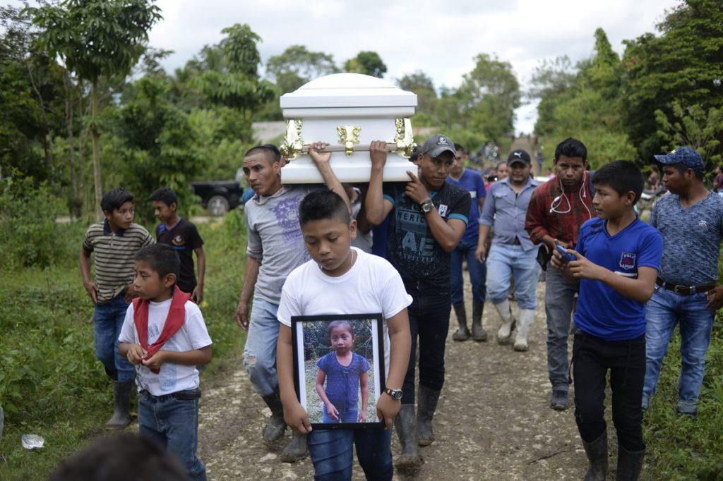 Un niño muestra una foto de Jakelin Caal, mientras encabeza el funeral, en Raxruhá, Alta Verapaz.