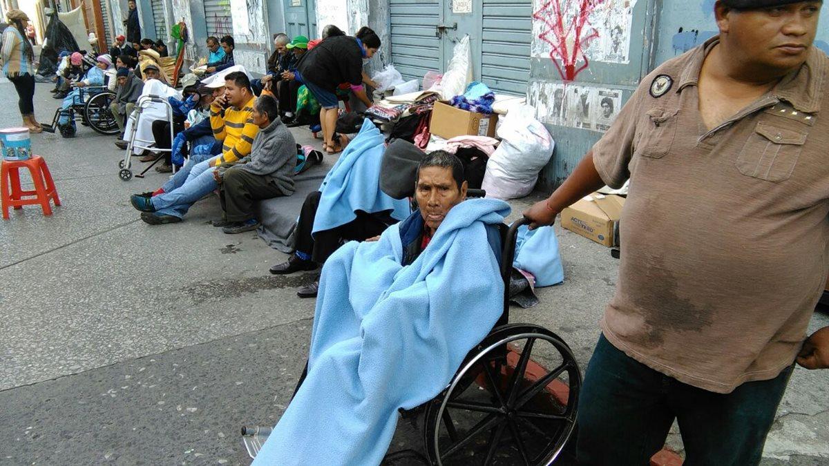 Ancianos, algunos en sillas de ruedas, permanecen frente al Congreso, exigiendo presupuesto para el hogar Dulce Refugio. (Foto Prensa Libre: Estuardo Paredes)