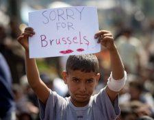 El niño expresa su solidaridad con las víctimas de los ataques terroristas en Bruselas en la frontera entre Grecia y Macedonia, cerca de Idomeni. (Foto Prensa Libre: AFP).