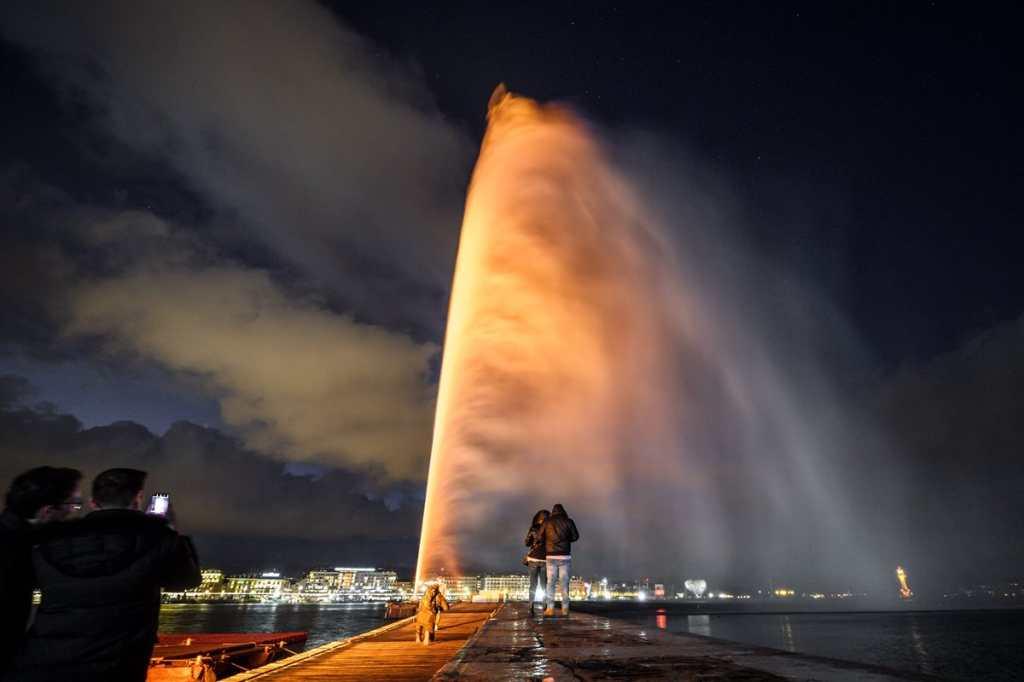 """La histórica Fuente de Ginebra (llamada """"Jet d'Eau"""" en francés), de 140 metros de alto, está iluminada en naranja para conmemorar el Día Internacional para la Eliminación de la Violencia contra las Mujeres."""