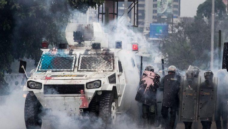 Una de las últimas modalidades de manifestantes es lanzar pintura a las fuerzas de seguridad en Venezuela. (Foto Prensa Libre: EFE)