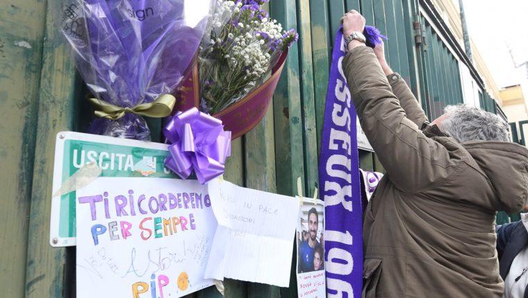 Una seguidora de la Fiorentina coloca una bufanda de Astori en una de las puertas del estadio. (Foto Prensa Libre: AFP)