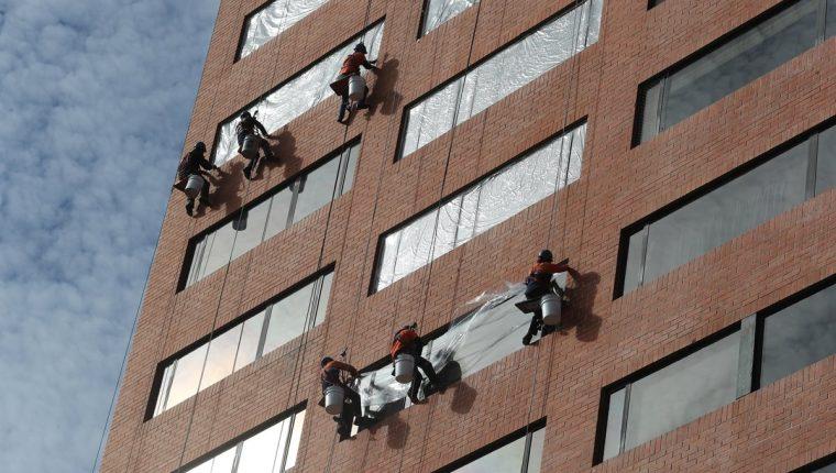 Empleados limpian vidrios en un edificio de la zona 10. (Foto Prensa Libre: Érick Ávila)