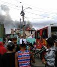 Bomberos tratan de apagar las llamas mientras que los vecinos salen con sus pertenencias. (Foto Prensa Libre)