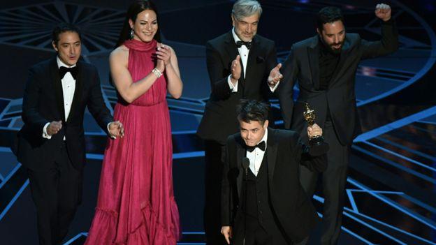 """El director Sebastián Lelio recibe el Oscar a mejor película de habla no inglesa acompañado del elenco de """"Una mujer fantástica"""". AFP"""