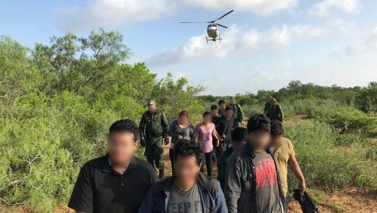 Migrantes aprehendidos en la frontera sur de EE. UU. son custodiados por guardias de la Patrulla Fronteriza. (Foto: CBP)