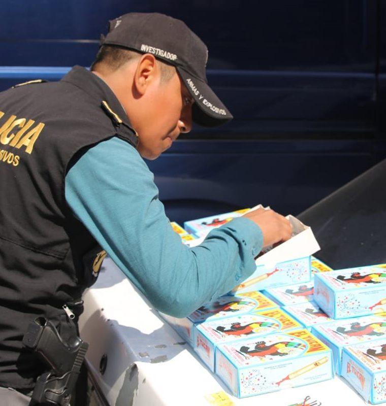Un agente de la Unidad de Explosivos de la PNC inspecciona los canchinflines decomisados en la zona 1. (Foto Prensa Libre: Cortesía)