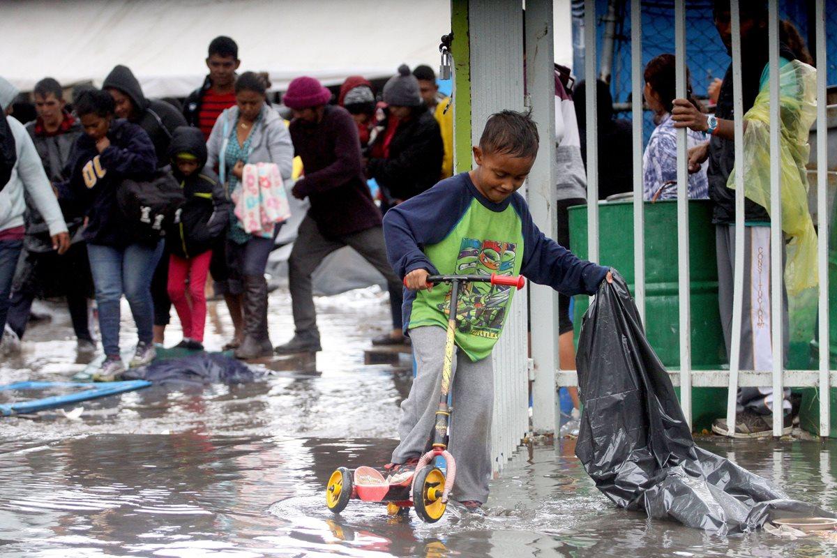 Un niño juega bajo la lluvia luego de que el albergue en el que se concentraban los integrantes de la caravana migrante se inundara. La Unicef expresa preocupación por estos menores. (Foto Prensa Libre: EFE