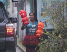 Una mujer ofrece a los automovilistas alcancías plásticas del personaje Mario Bros a Q15, en la zona 9. (Foto Prensa Libre: Erick Ávila)