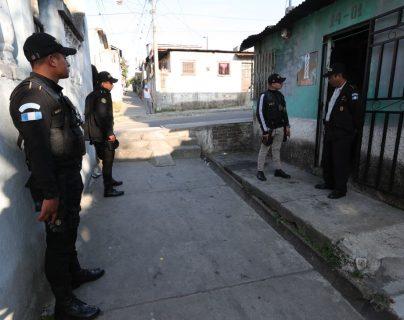 Agentes de la PNC resguardan viviendas durante allanamientos en la capital y al menos siete departamentos. (Foto Prensa Libre: Estuardo Paredes)