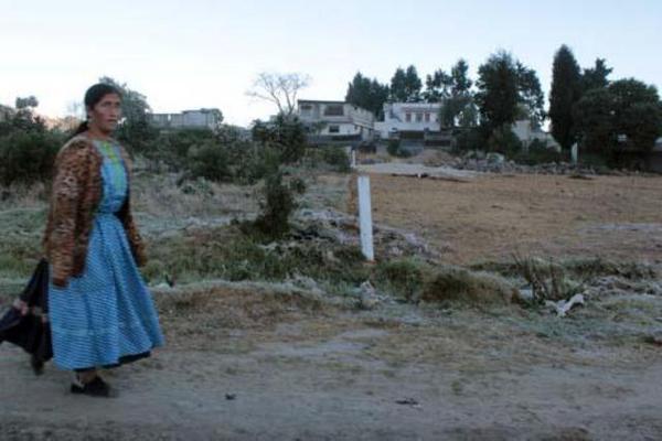 """Mujer camina en un sector con escarcha, debido el descenso de la temperatura, en Quetzaltenango. (Foto Prensa Libre: Carlos Ventura) <br _mce_bogus=""""1""""/>"""