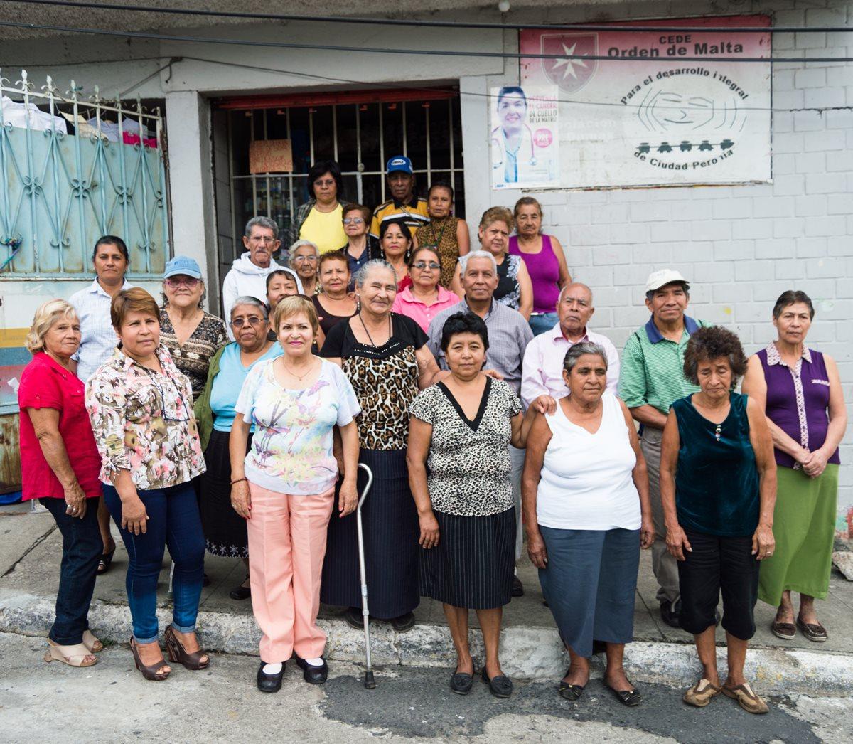 Mayra Escobar (con pantalón de lona y blusa estampada) y algunas integrantes de la asociación posan con varios abuelitos a los que ayudan. Foto Prensa Libre: Roberto Villalobos Viato.