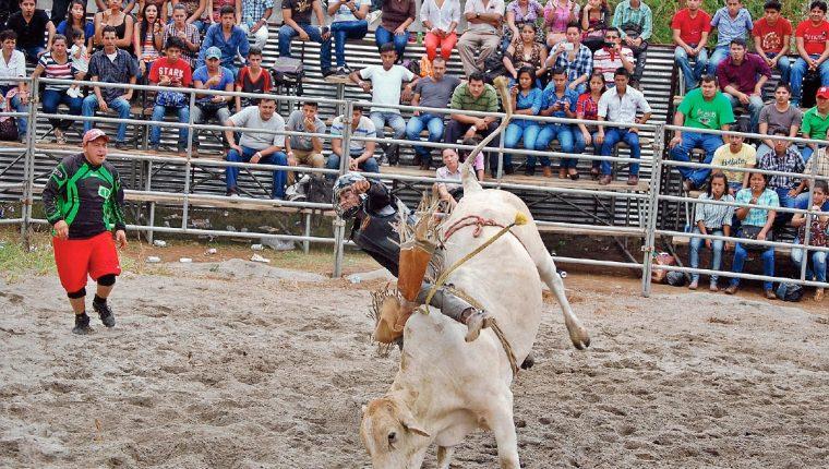 Estudiante lucha por mantenerse en el lomo de un toro, durante el rodeo organizado por la Universidad Rural en Coatepeque, Quetzaltenango. (Alexánder Coyoy)