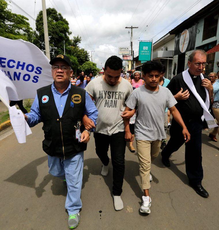 Dos hombres (c) -que habían sido arrestados en recientes protestas- caminan junto a un sacerdote y integrante de la Asociación Nicaragüense de Derechos Humanos (ANPDH) después de ser liberados de la cárcel en Masaya, Nicaragua. (EFE).