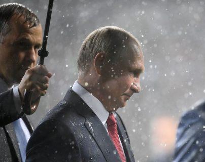 El presidente de Rusia fue el único que tuvo paraguas de la organización o de su servicio de seguridad. Minutos después reaccionaron para cubrir a los otros mandatarios. (Foto Prensa Libre: AFP)