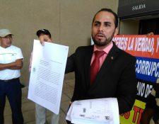 El abogado Elmer Salguero muestra, afuera de la sede central del MP, copias de denuncias y actas electorales. (Foto, Prensa Libre: Rosa María Bolaños).