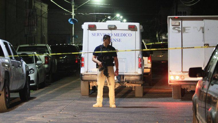 Un policía monta guardia en el lugar donde peritos forenses recogen información en torno al sitio donde 15 personas aparecieron muertas.(Foto Prensa Libre:AFP).
